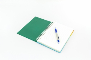 Open green book with pen on white background.